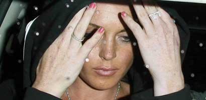 Lindsay Lohan hides her face